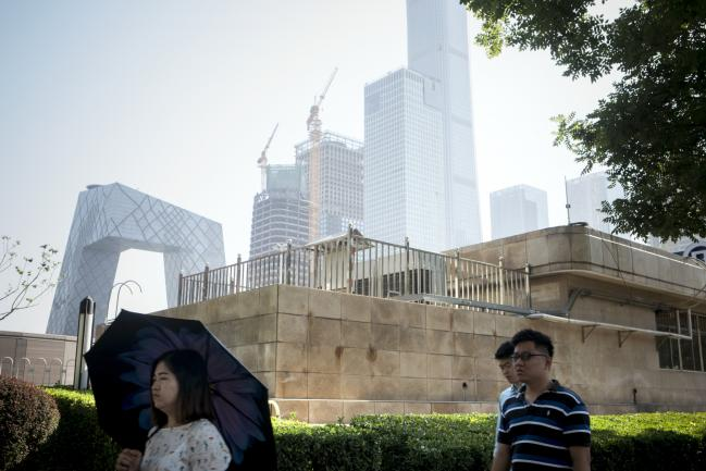 © Bloomberg. Pedestrians walk along a street near the China Central Television (CCTV) headquarters building, left, and other buildings in the central business district in Beijing, China, on Friday, June 1, 2018. The People's Bank of China announced on Friday that it would add debt instruments tied to small-business and the green economy. Photographer: Giulia Marchi/Bloomberg