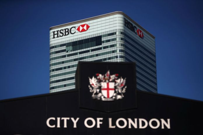 © Reuters. HSBC's building in Canary Wharf is seen behind a City of London sign outside Billingsgate Market in London