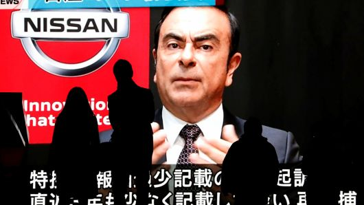 Passersby are silhouetted as a huge street monitor broadcasts news reporting ousted Nissan Motor chairman Carlos Ghosn's indictment and re-arrest in Tokyo, Japan December 10, 2018.