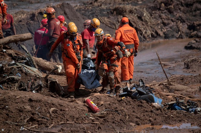 Firefighters recover a body following the collapse last month of Dam 1.