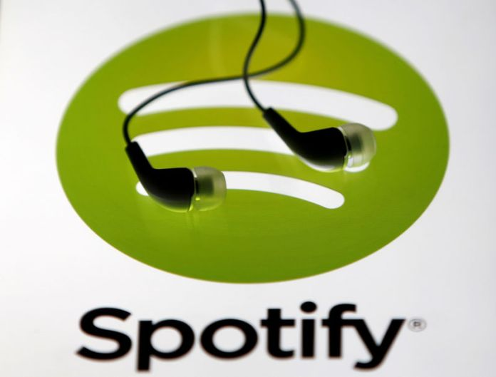 © Reuters. Earphones are seen on a tablet screen with a Spotify logo on it, in Zenica