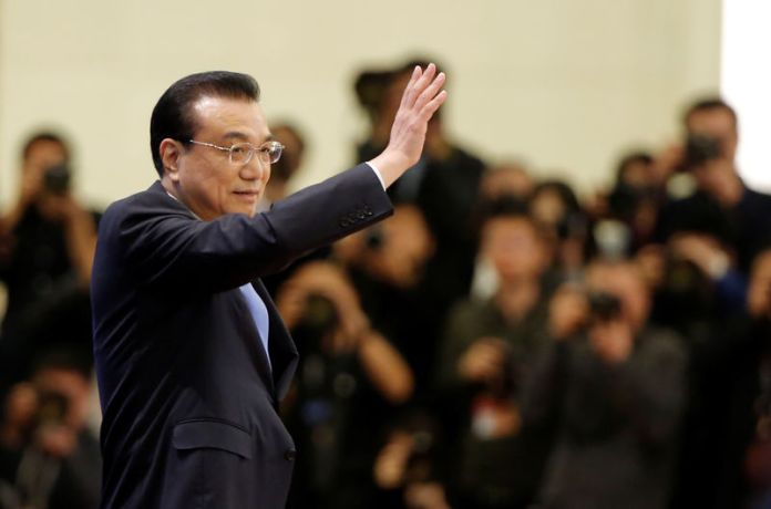 © Reuters. Chinese Premier Li Keqiang waves as he arrives for a news conference following the closing session of the National People's Congress (NPC) at the Great Hall of the People in Beijing