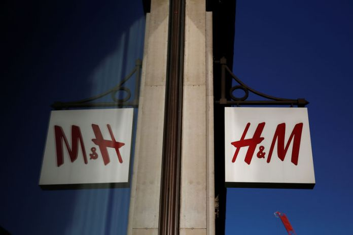 © Reuters. FILE PHOTO: A logo is reflected in the window as it hangs outside the H&M store on Oxford Street in London