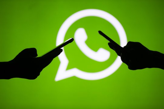 ANKARA, TURKEY - JULY 18 : People hold mobile phones in front of the logo of WhatsApp application in Ankara, Turkey on July 18, 2018. (Photo by Aytac Unal/Anadolu Agency/Getty Images)