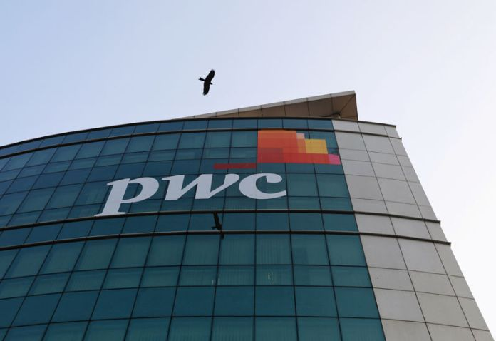 © Reuters. A bird flies past the logo of Price Waterhouse installed on the facade of its office in Mumbai