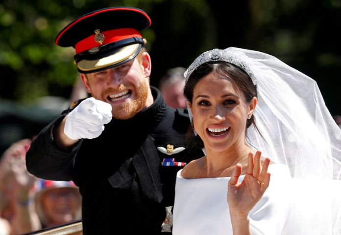 © Reuters. FILE PHOTO: Britain's Prince Harry gestures next to his wife Meghan as they ride a horse-drawn carriage after their wedding ceremony at St George's Chapel
