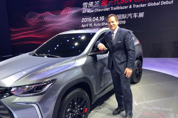 © Reuters. Doug Houlihan, chief engineer of GEM project, poses for photo next to GM's Chevrolet Tracker unveiled at the Shanghai auto show