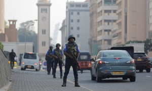 Sri Lankan military personnel stand guard on a main road near the president's house in Colombo.
