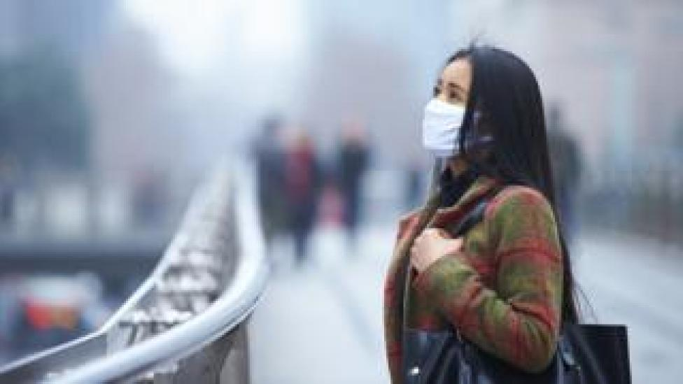 Woman wearing face mask in polluted city
