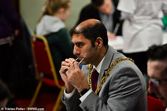 Mayor of Worcester Jabba Riaz swabs his mouth with two buds at the event in Worcester where more than 1,000 people turned out