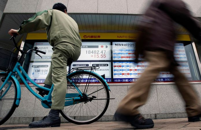 © Reuters. FILE PHOTO: A man riding on a bicycle looks at an electronic board showing the Japan's Nikkei average outside a brokerage in Tokyo