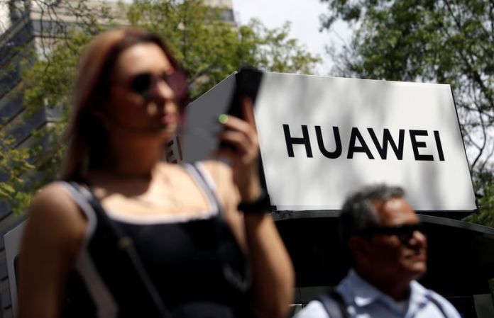 © Reuters. People walk past a Huawei company logo at a bus stop in Mexico City