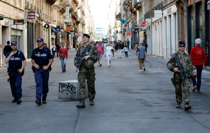 © Reuters. Police and army patrol the streets during the manhunt of a suspected suitcase bomber in central Lyon