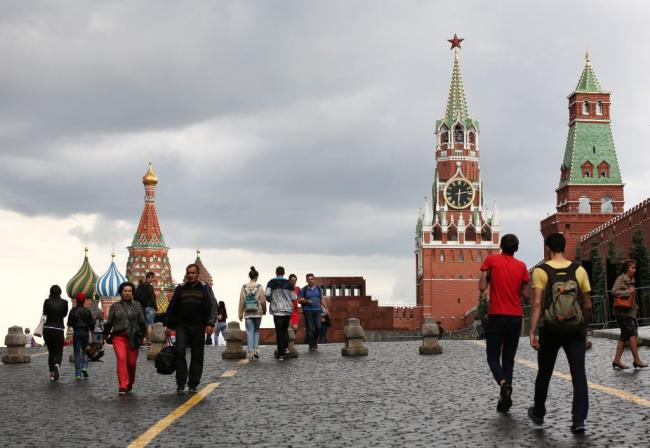 © Bloomberg. The Kremlin clock sits on the Spasskaya tower, center, near St. Basil's cathedral, left, on Red Square in Moscow, Russia, on Wednesday, July 5, 2017. U.S. officials, including Brett McGurk, the U.S. envoy for the coalition to fight the Islamic State, have been quietly meeting with Russian counterparts for weeks to lay the groundwork for cooperation.