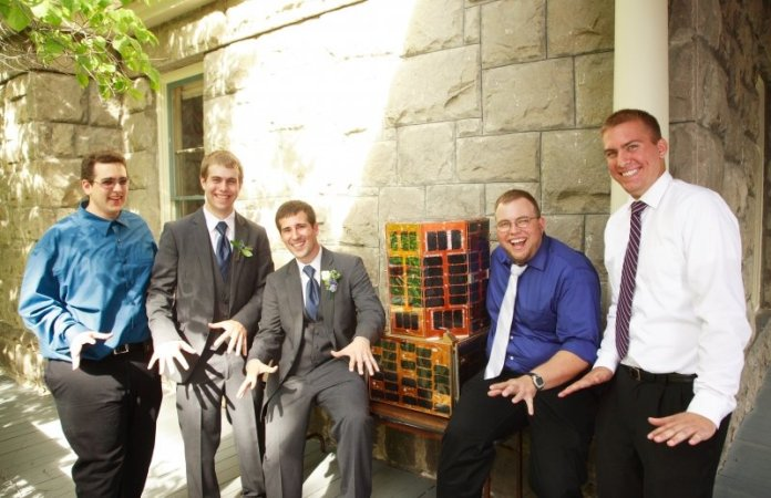 Five men in weddig attire, including two in tuxedos, show jazz hands in a sunny courtyard with a satellite on a table and a gray stone wall, white pillar and green tree in the far upper left, in the background. They are all smiling.