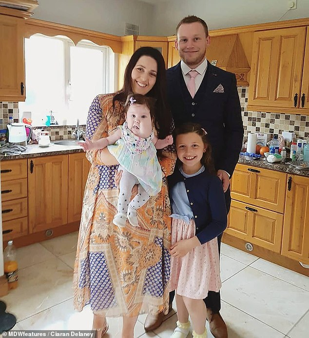 Evie was unable to breathe for herself after she was delivered, with doctors saying the cysts were blocking her airways (pictured with parents Ciaran Delaney, Katie Nolan and sister Aila)