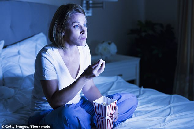 People who spend more than four hours binge-watching TV are at 50% greater risks of heart disease and early death because they tend to sit, un-moving, after eating a big meal, and often with fatty, salty snacks, a new study finds (file)