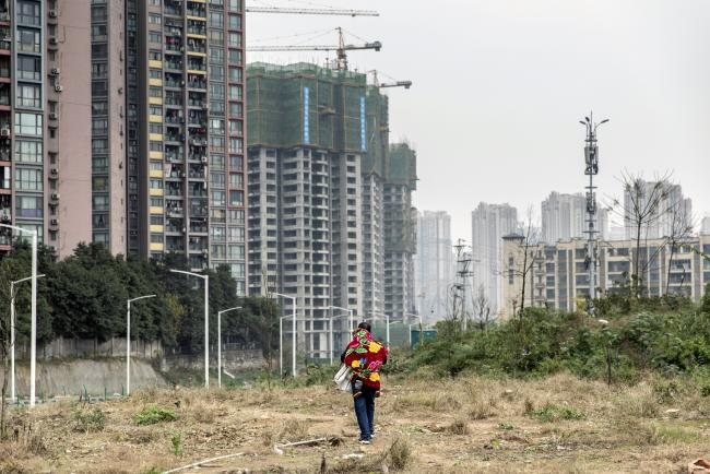 © Bloomberg. A man carrying a child on his back walks across a clearing past residential buildings on the outskirts of Chongqing, China, on Friday, Jan. 4, 2019. U.S. and Chinese officials began trade negotiations in the hope of reaching a deal during a 90-day truce between President Donald Trump and his counterpart Xi Jinping reached in early December. Photographer: Qilai Shen/Bloomberg