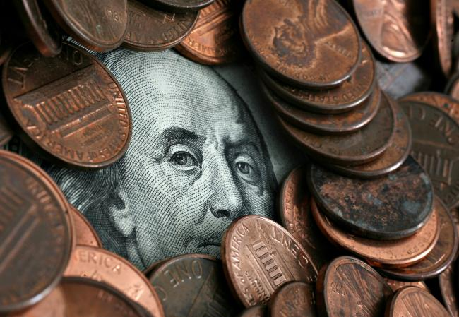 © Bloomberg. UNITED STATES - MAY 07: A portrait of Benjamin Franklin, printed on the face of U.S. one hundred dollar bill, is obscured beneath pennies in a photograph arranged on Monday, May 7, 2007, in New York. The dollar traded within a cent of its all-time low against the euro before a U.S. report forecast by economists to show new-home sales fell last month. (Photo by Stephen Hilger/Bloomberg via Getty Images)