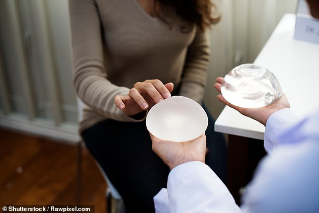 Women who suffer from severe pain due to hardening and shrinkage of the internal scar tissue – known as capsular contracture – may be eligible to have their implants removed on the NHS. Otherwise, they have to pay about £3,500 (pictured, a woman examines a breast implant)
