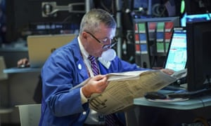 A trader reading the newspaper and blowing a bubble on the floor of the New York Stock Exchange yesterday