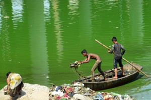 Indian workers collect and remove trash with a boat as they take part in the cleaning of the Sabarmati river in Ahmedabad on May 21, 2019.