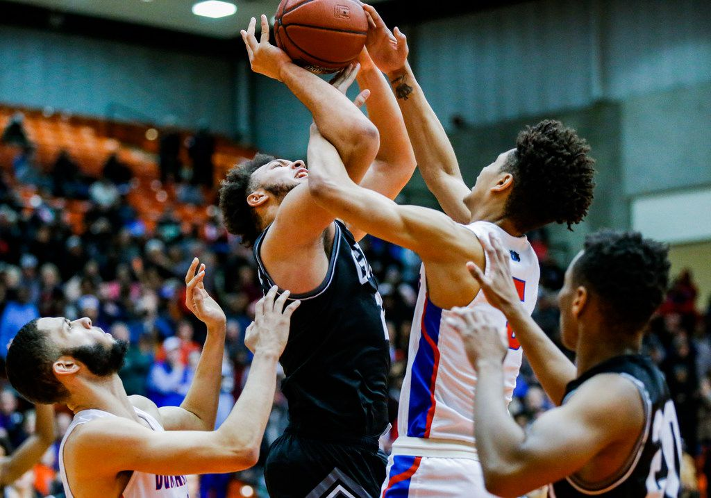 Denton Guyer junior forward JaKobe Coles, center left, and Duncanville junior guard Micah Peavy, center right, battle for a rebound during overtime of the Class 6A Region I championship boys basketball game at the Wilkerson-Greines Athletic Center in Fort Worth, Saturday, March 2, 2019. Duncanville won in overtime 66-62. (Brandon Wade/Special Contributor)