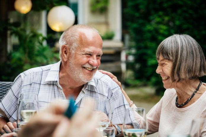 Elderly Couple Smiling At Family BBQ