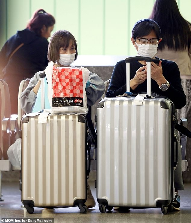 Arriving passengers from Asia, airline staff and airport staff at Los Angeles International Airport take precautionary measures donning face masks on Friday