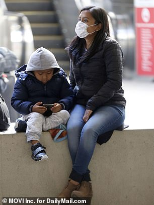 The CDC also issues its highest warning to level 3, which urges Americans to 'avoid unessential travel.' Pictured: Travelers with masks at Los Angeles International Airport on Friday