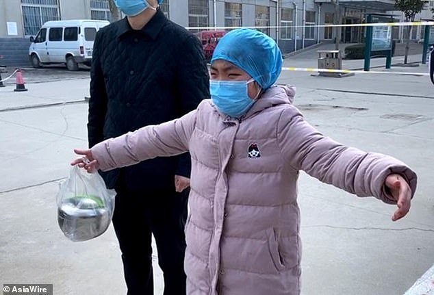 Her nine-year-old daughter Cheng Shiwen cries from a distance as she is reunited with her mother