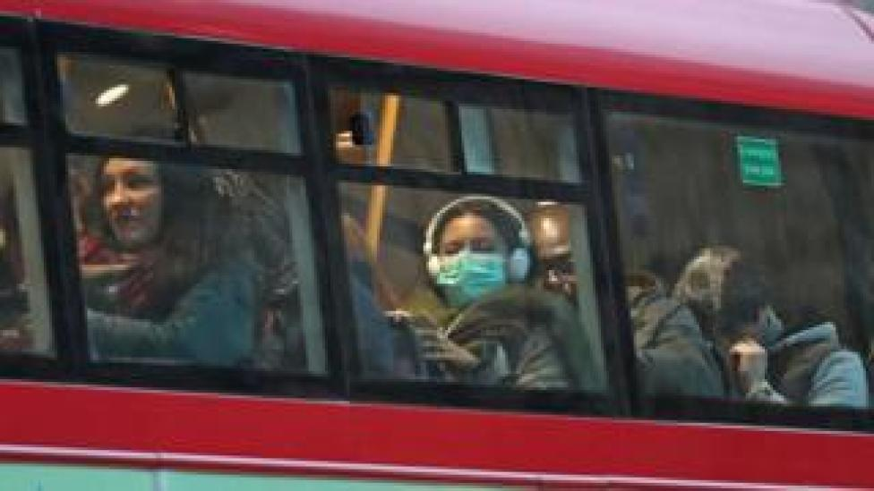 A woman wearing a face mask on a bus in London, as the first case of coronavirus has been confirmed in Wales and two more were identified in England