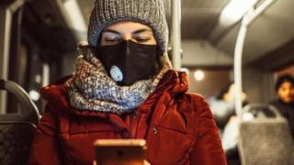 Woman wearing mask looking at mobile phone