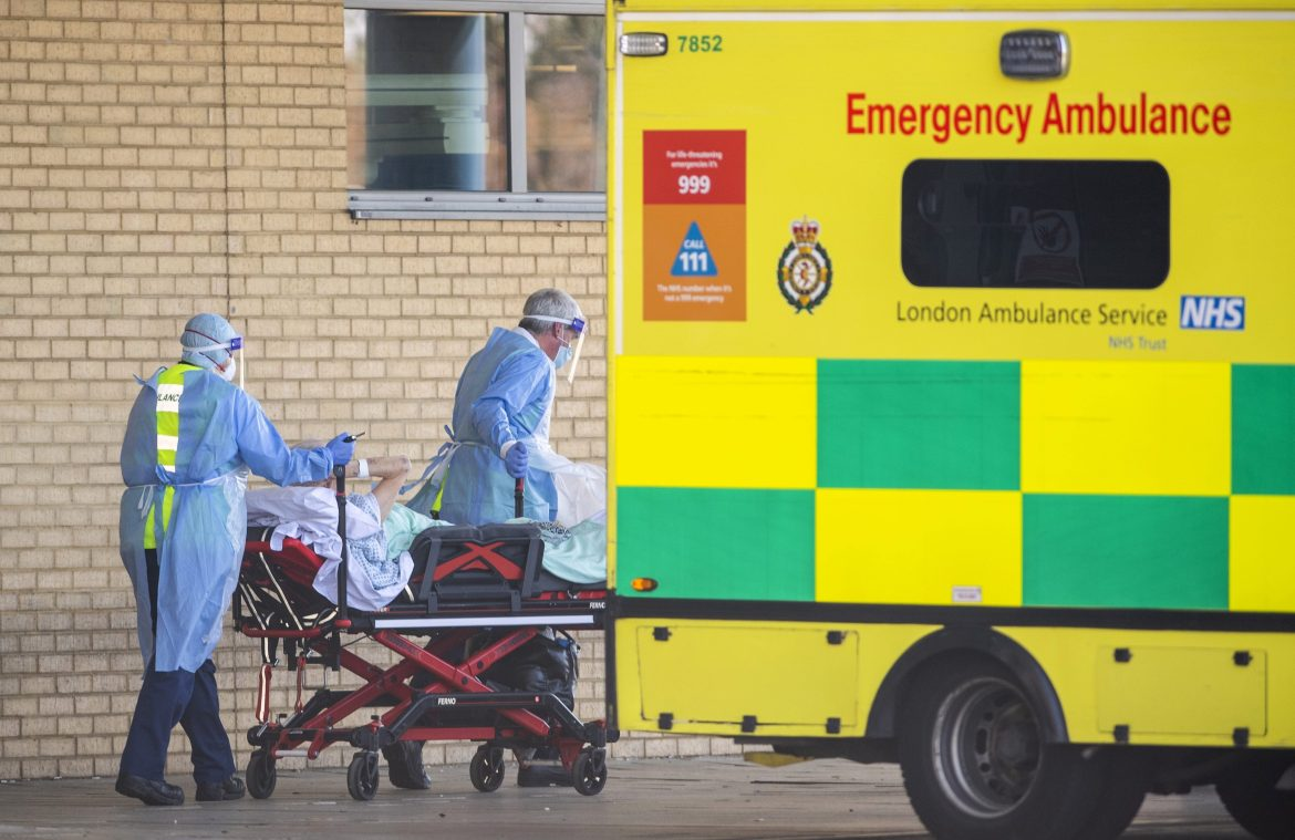 NHS workers transport a patient into Queens Hospital in Romford, east London