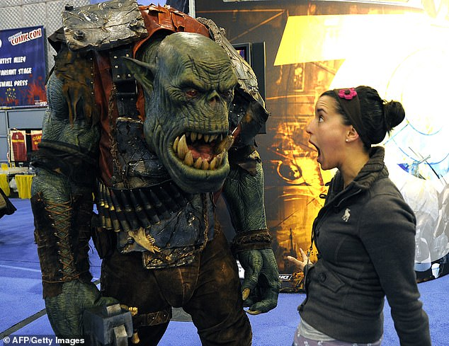(Pictured) A Comic Con convention-goer stands next to an Orc from the Warhammer 40,000 series. Games Workshop is the maker of the Warhammer fantasy miniatures game