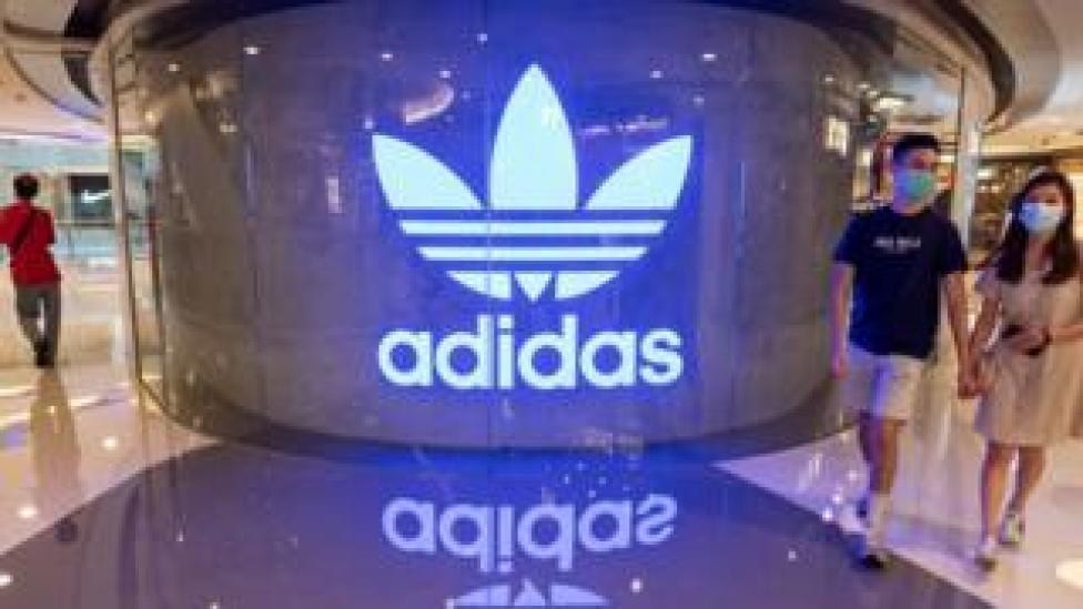 Shoppers wearing face masks walk past an Adidas logo at a shopping mall.