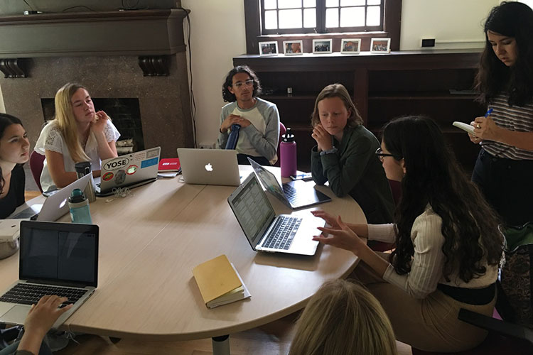 Students at UC Berkeley's Human Rights Center Investigations Lab sit at a round table, their laptops open, discussing their work.