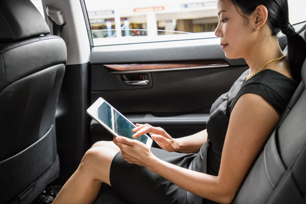 Woman sitting in a car working on a tablet computer