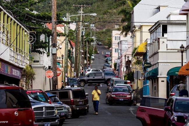 © Bloomberg. A pedestrian speaks on a mobile device while walking along a street in the town of Christiansted in Saint Croix, Virgin Islands.