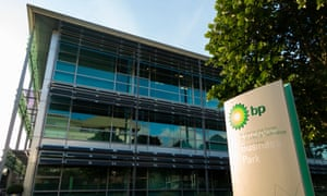 Picture of a modern office building with a BP sign in front of it in sunlight