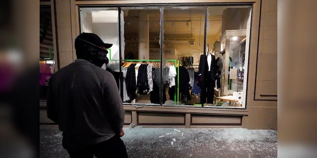 A man stands in front of a broken display window at a retail store during protests in Portland, Ore., Wednesday, Nov. 4, 2020, following Tuesday's election.