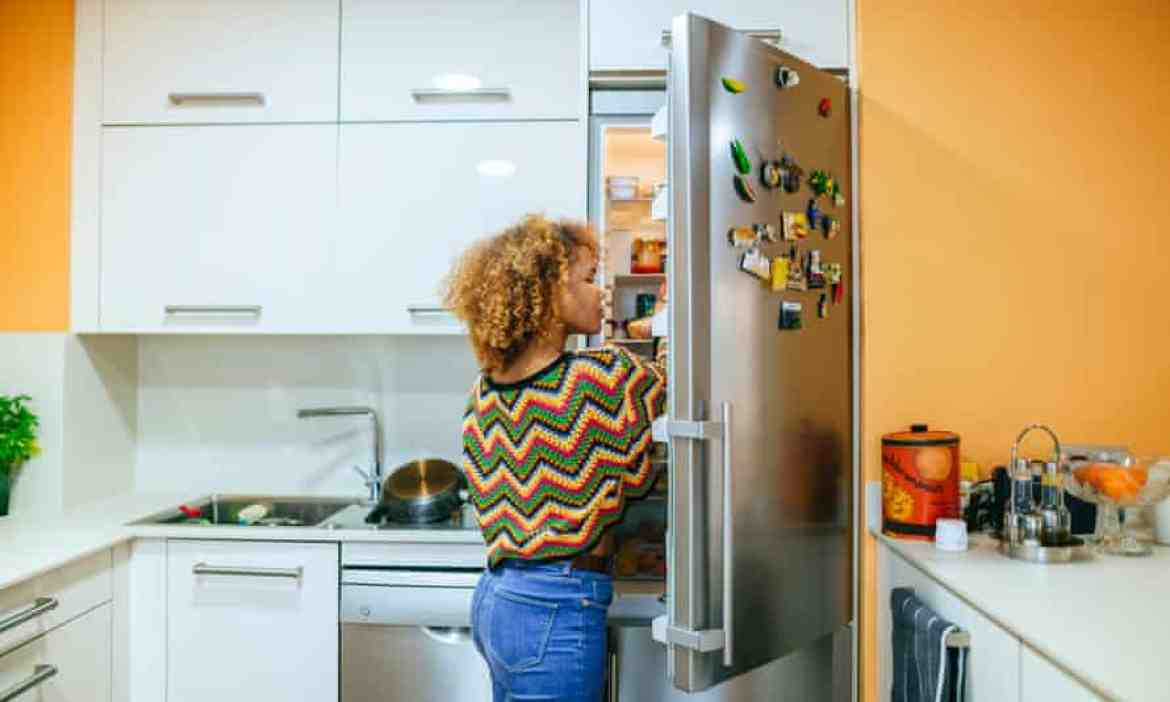 Woman opens the fridge in her kitchen