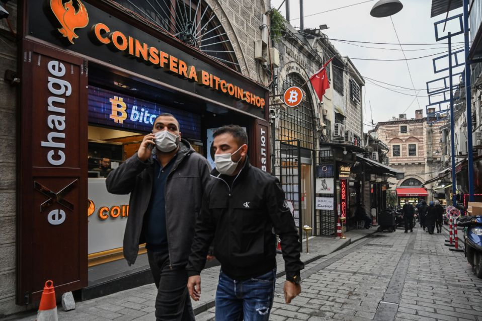 "People pass in front of a crypto currency ""Bitcoin Change"" shop near the Grand Bazaar on December 17, 2020 in Istanbul. - Leading virtual currency bitcoin on 16 December traded above $20,000 for the first time following a sustained run higher in recent weeks. Bitcoin reached a record-high $20,398.50 before pulling back to $20,145, which was still an intra-day gain of nearly four percent. (Photo by Ozan KOSE / AFP) (Photo by OZAN KOSE/AFP via Getty Images)"