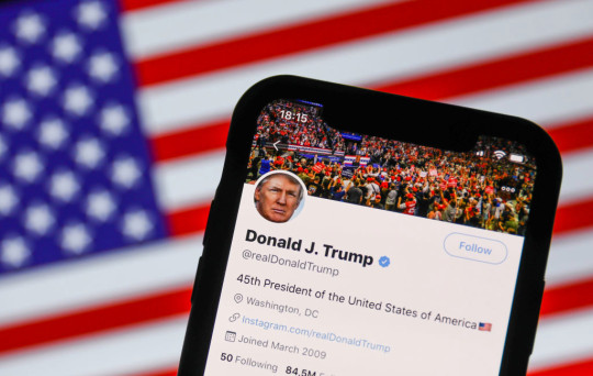 Donald Trump's Twitter account in front of the US flag