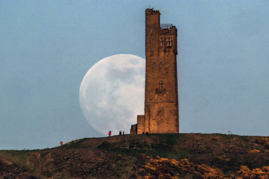 A full moon seen rising behind Victoria Tower on Castle Hill in Huddersfield, England (Photo by Anthony Devlin/Getty Images)
