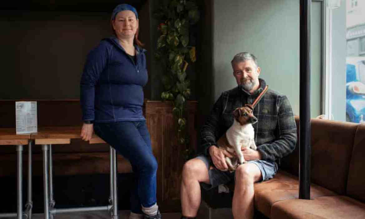Vicky Irwin and Greg Daniel, who has a dog on his lap, inside their empty coffee shop
