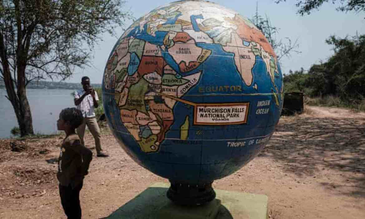 A boy stands by a globe statue at the Murchison Falls national park in Uganda.