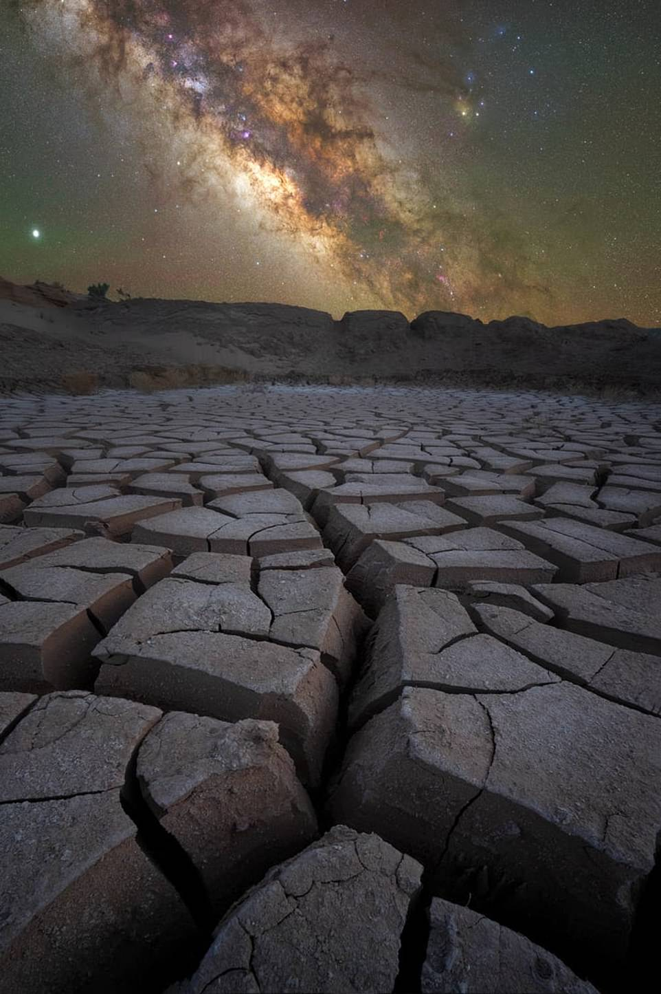 'Desolation'— by Phil Sisto in the Capitol Reef National Park, Utah. Mr Sisto said: 'This image was captured in the remote Cathedral Valley District of the park. I placed my camera low to the ground, exaggerating the otherworldly mud cracks with my wide-angle lens, and shot the sky with a longer lens as a panorama on my star tracker'