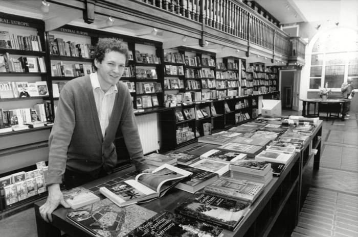 A black-and-white photograph of bookseller James Daunt in his first shop in 1990.