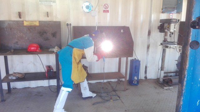 A student demostrating how they weld a 4G pipe at the Bahimba Technical Institute in Hoima.